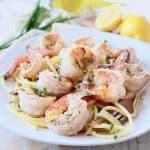 Shrimp on top of pasta on plate with gold fork swirling pasta on the side of the plate
