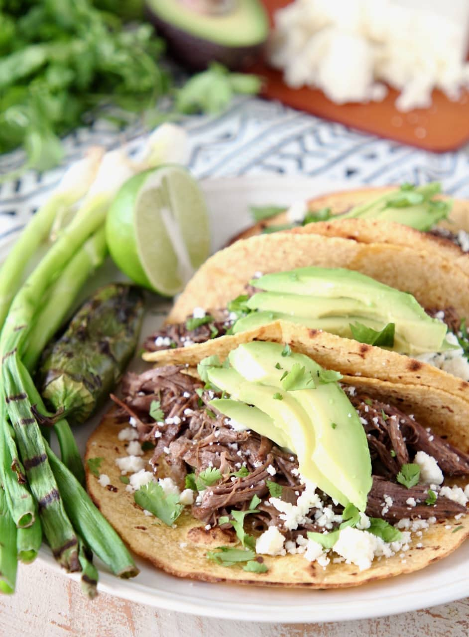 Slow Cooker Shredded Beef Barbacoa Tacos with Grilled Green Onions, Sliced Avocado, Cilantro and Cotija Cheese
