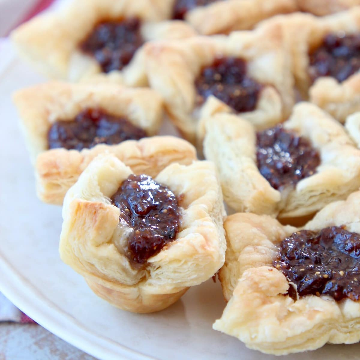 Fig jam and brie in baked puff pastry bites on plate