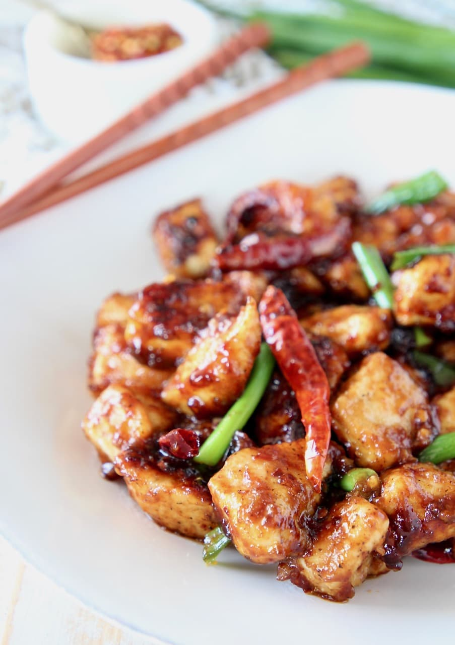 Gluten free general tso chicken with red chili peppers and green onions on white plate with wood chopsticks