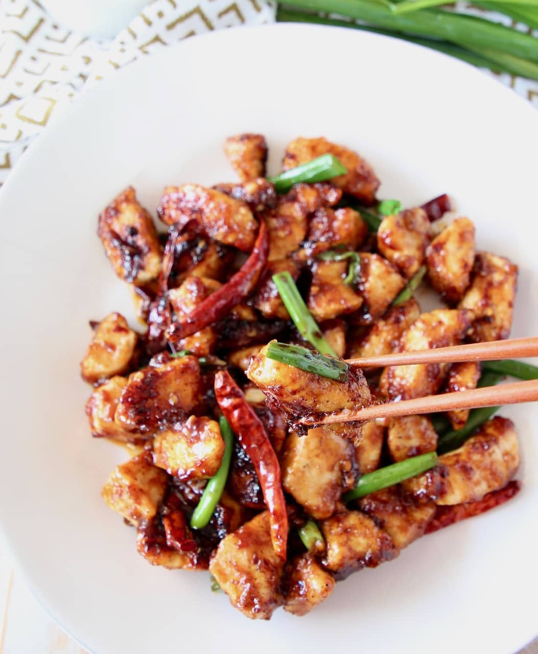 General tso chicken on a white plate with chopsticks picking up a piece of chicken