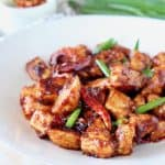 General Tso chicken with red chilies and green onions on white plate