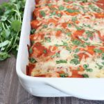 Creamy Sriracha Beef Enchiladas Recipe with Melted Cheese and Cilantro in baking dish