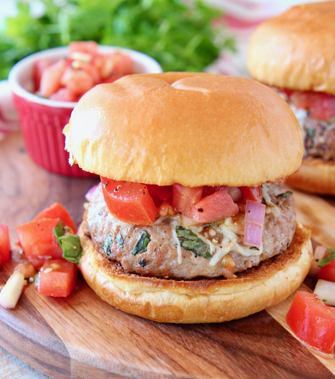Turkey burger on bun topped with diced tomatoes and onions on wood cutting board