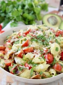 Pasta salad in bowl with sliced cherry tomatoes