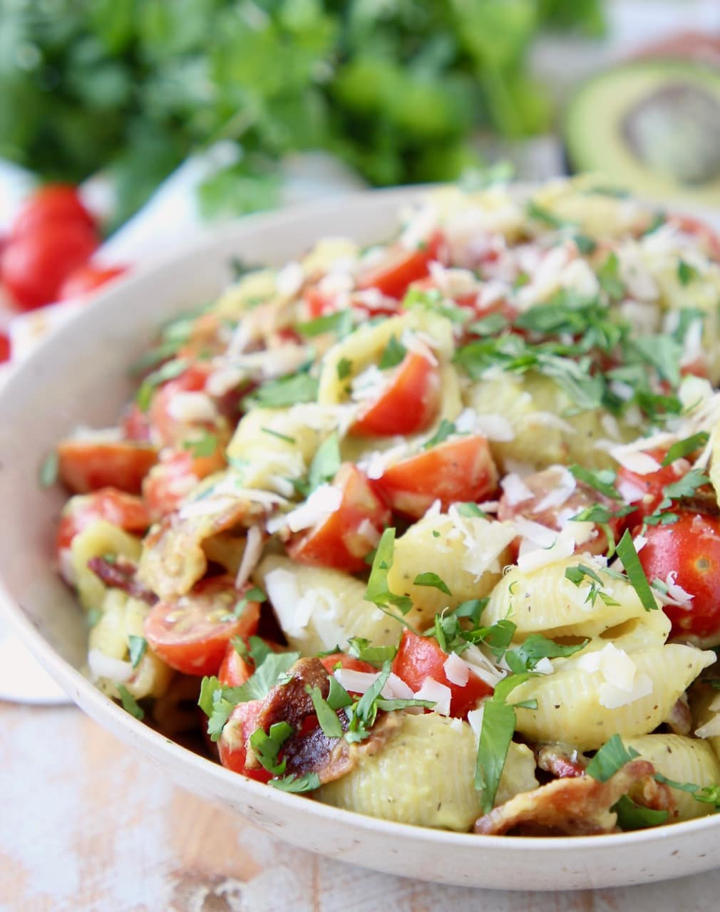 Pasta salad in bowl with bacon, tomatoes and parmesan cheese