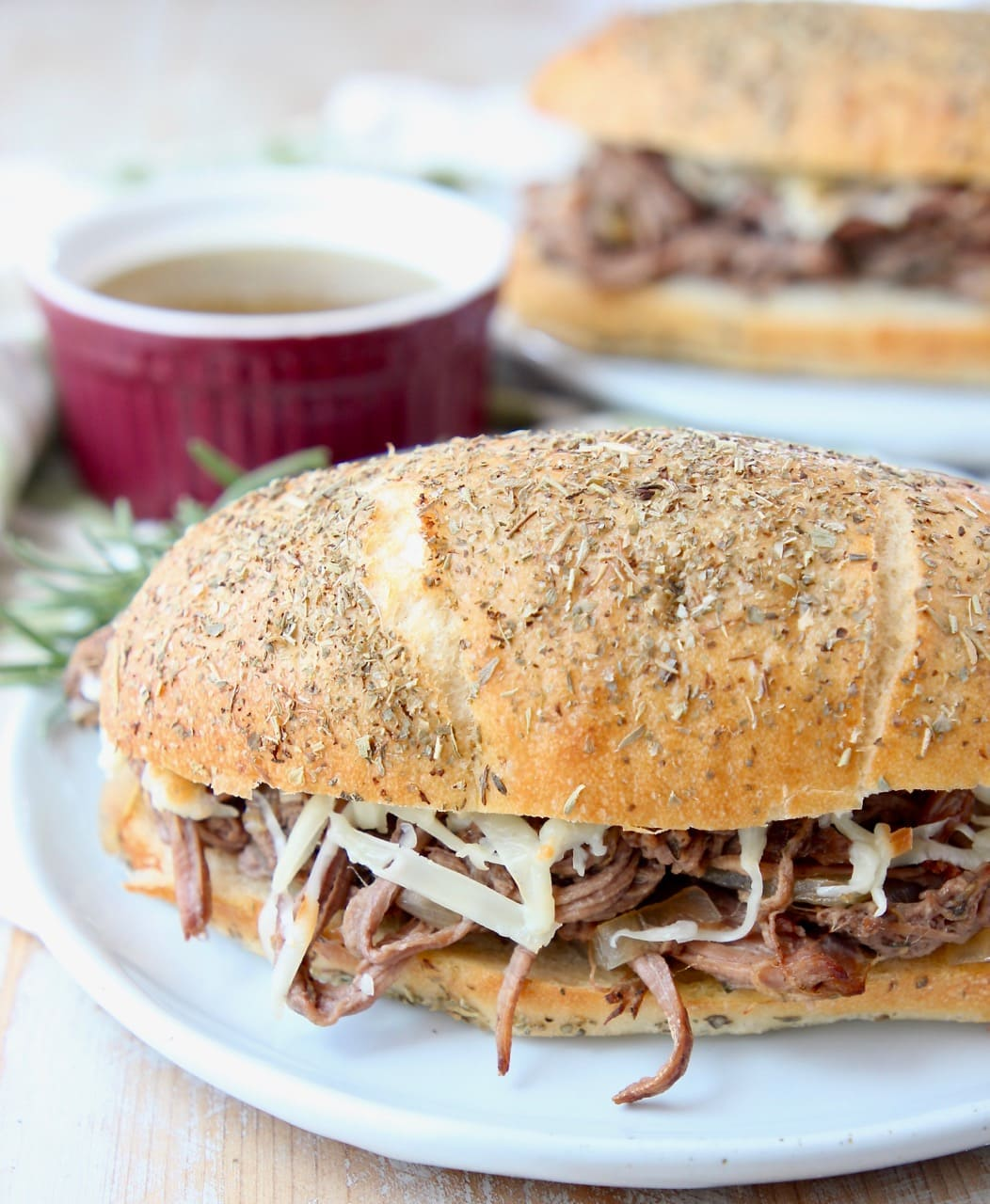 Shredded tri tip sandwich on plate with bowl of au jus