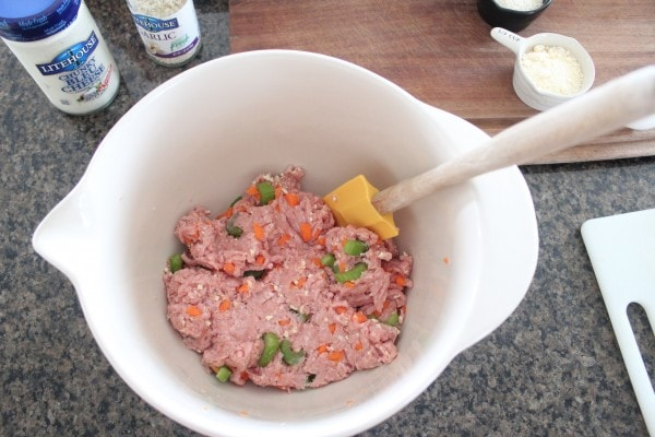 ground turkey and celery and carrots being mixed by a spatula in a white bowl