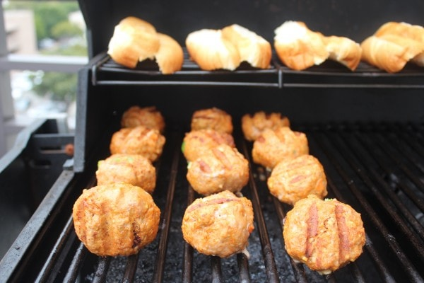 Meatballs and hot dog buns on a grill