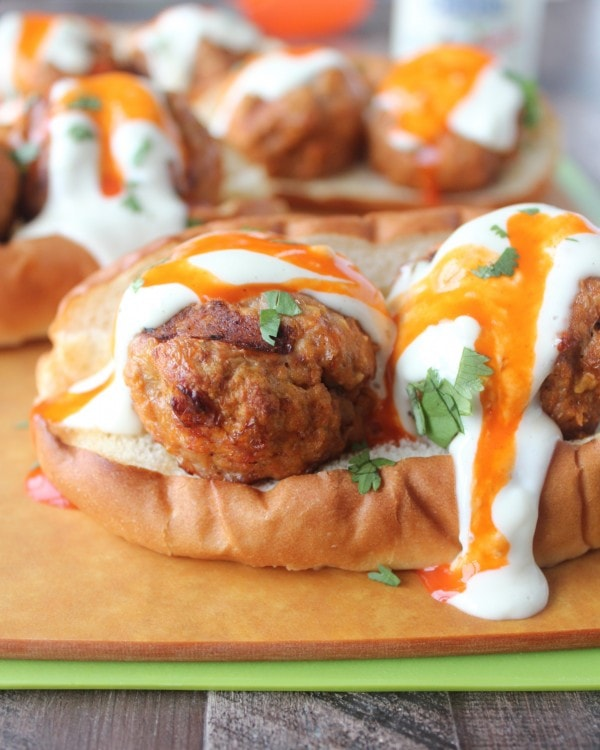 Hot dog bun topped with meatballs and drizzled with buffalo sauce and blue cheese dressing.