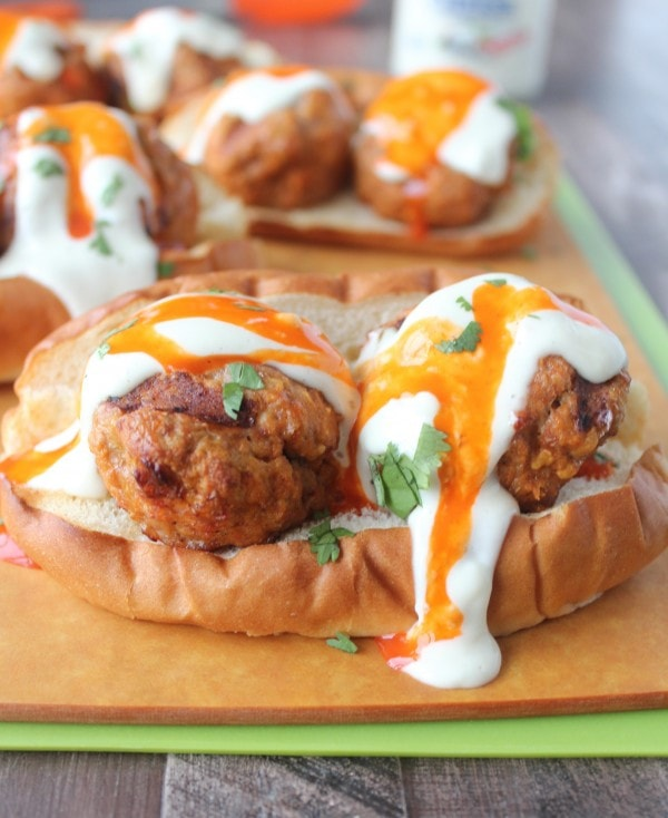 Hot dog bun topped with turkey meatballs and drizzled with buffalo sauce and blue cheese dressing.