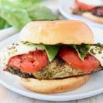 Caprese grilled chicken sandwich on white plate with fresh basil in background