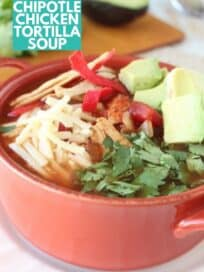 chicken tortilla soup in orange bowl, topped with diced avocado, shredded cheese and cilantro
