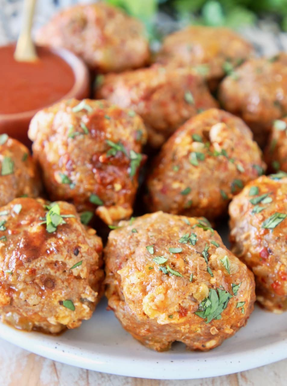 Taco meatballs on plate with small bowl of hot sauce
