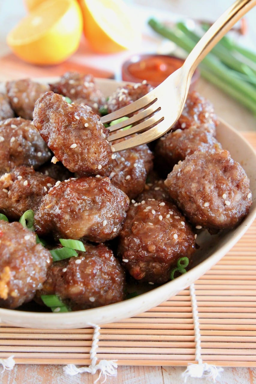 Chinese Meatballs in bowl, with gold fork holding up one meatball