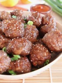 Chinese orange glazed meatballs in bowl with sesame seeds and green onions on top