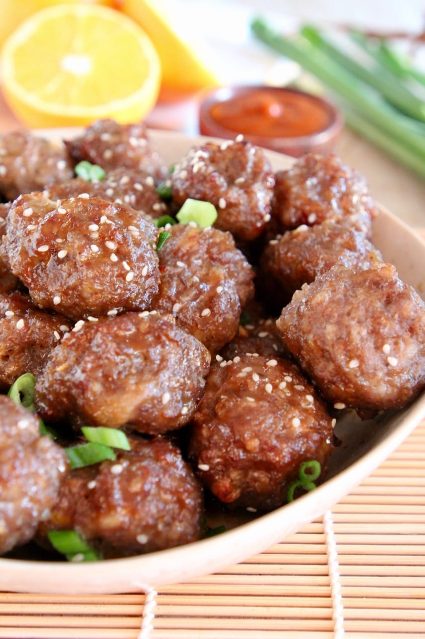 Chinese meatballs in bowl with diced green onions and sesame seeds
