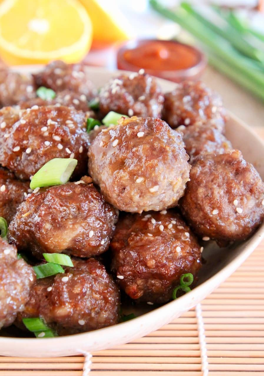 Chinese meatballs in bowl, topped with sesame seeds and green onions