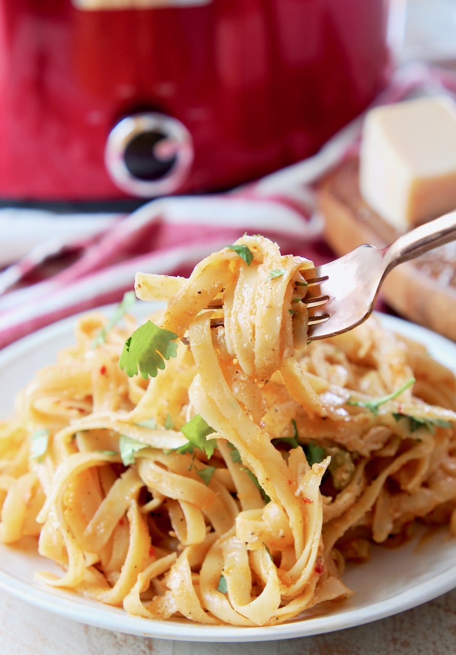 Crock pot chicken alfredo on plate, with a fork wrapped in noodles lifting off the plate and red crock pot in background