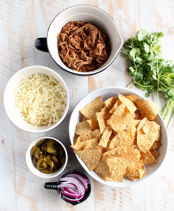 The Ultimate Pulled Pork Nachos Recipe Ingredients in bowls; chips, sliced red onions, jalapeños, cheese, pulled pork, and cilantro