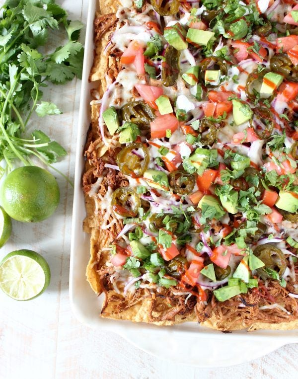 A white dish filled with tortilla chips topped with pulled pork, cheese, onions, tomatoes, and avocado on a wooden surface next to limes and cilantro.