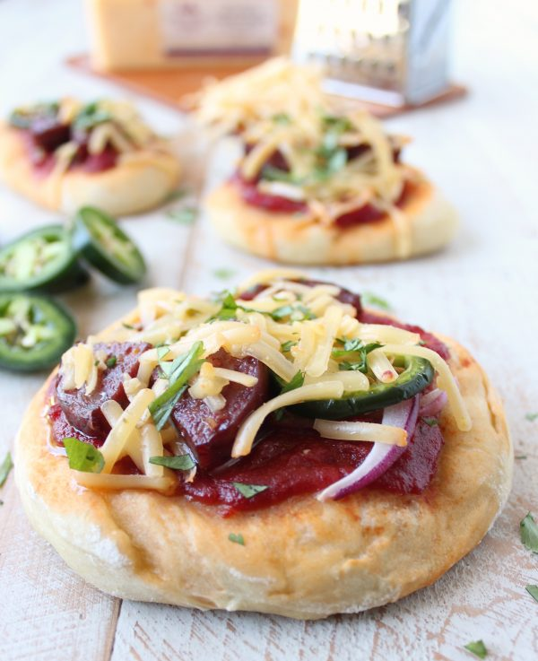 Sriracha pizza sauce, jalapenos, summer sausage and jalapeno cheddar cheese top this delicious mini pizza recipe, perfect for game days and parties!