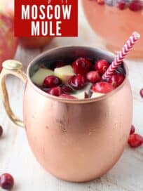 Moscow mule with fresh cranberries and diced apples in copper mug