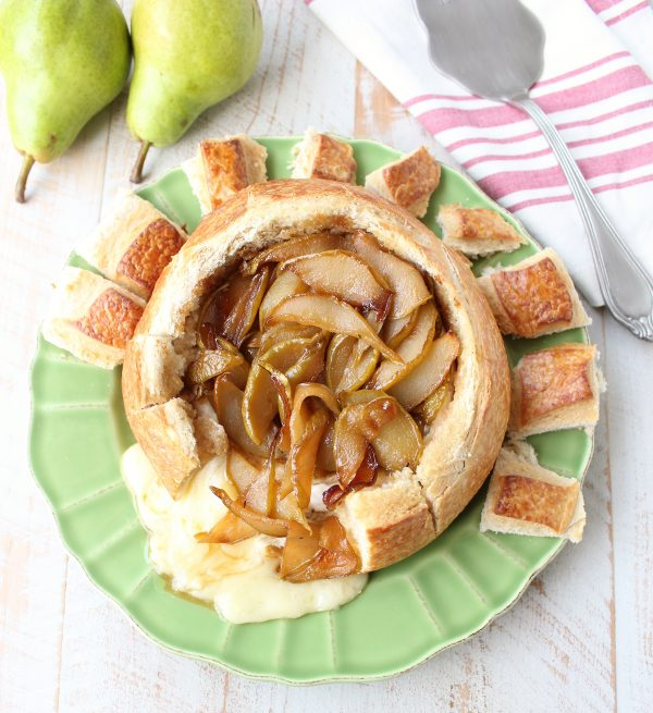 Caramelized pears on baked brie bread bowl on green plate with fresh pears