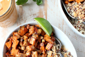 Overhead picture of roasted sweet potato, quinoa and peanut sauce in a bowl with a fork