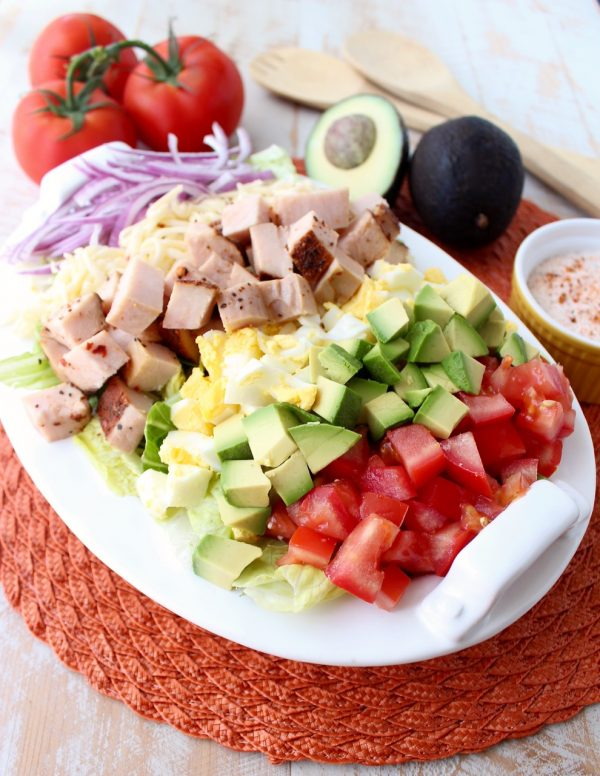 This gluten free Cobb Salad recipe is colorful, flavorful & so easy to make! It's topped with Cajun turkey, avocado, tomatoes & creamy Cajun ranch dressing!