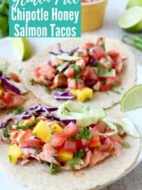 salmon tacos on plate topped with mango salsa