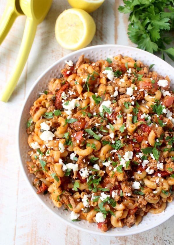 In just one pot and under 45 minutes, make a delicious Greek Pasta recipe filled with sun dried tomatoes, ground turkey, capers and feta cheese!