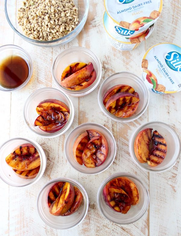 Cinnamon sugar grilled peaches are layered with peach almond milk yogurt and granola in this delicious vegan parfait recipe, great for breakfast or dessert!