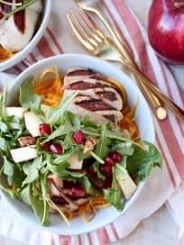 Grilled balsamic chicken & roasted butternut squash noodles are topped with a pomegranate apple arugula salad in this healthy, gluten free bowl recipe!