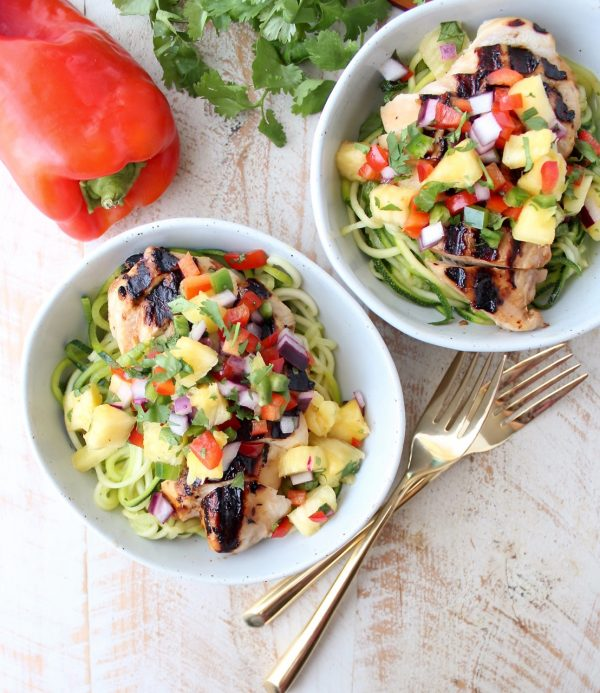 Grilled teriyaki chicken is served over zucchini noodles and topped with pineapple salsa in these healthy, gluten free and delicious zoodle bowls!