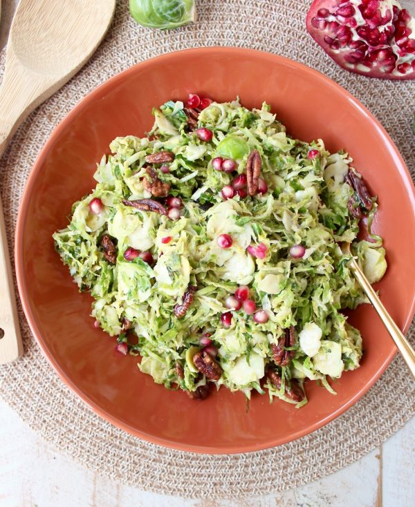 Serve this brussels sprout salad warm or cold as the perfect fall side dish! It's easy enough for weeknight dinners, but elegant enough for Thanksgiving dinner. This salad is tossed with a homemade dijon dressing, pomegranate seeds & pecans for a salad that's both colorful and flavorful!