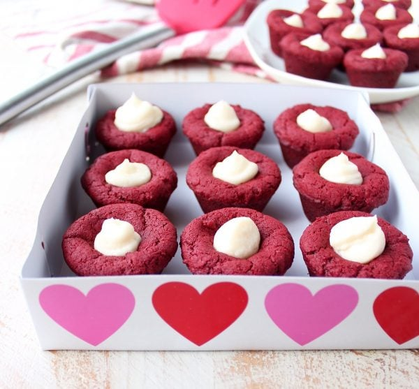 Red velvet cookie cups filled with cream cheese frosting are a delicious and adorable dessert recipe that's also easy to make! Perfect for Valentine's Day, birthdays or any day you're craving a sweet treat!