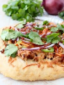 Turn your favorite banh mi sandwich into a pizza with this easy and delicious Banh Mi Pizza recipe, topped with sesame ginger ground pork, fresh carrots, jalapeños, cilantro and Sriracha!