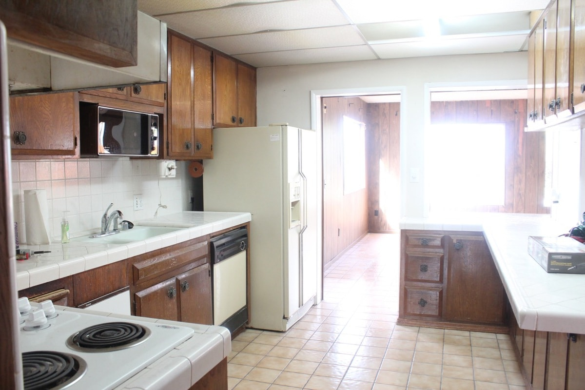 Old kitchen with tile floors and brown wood cabinets