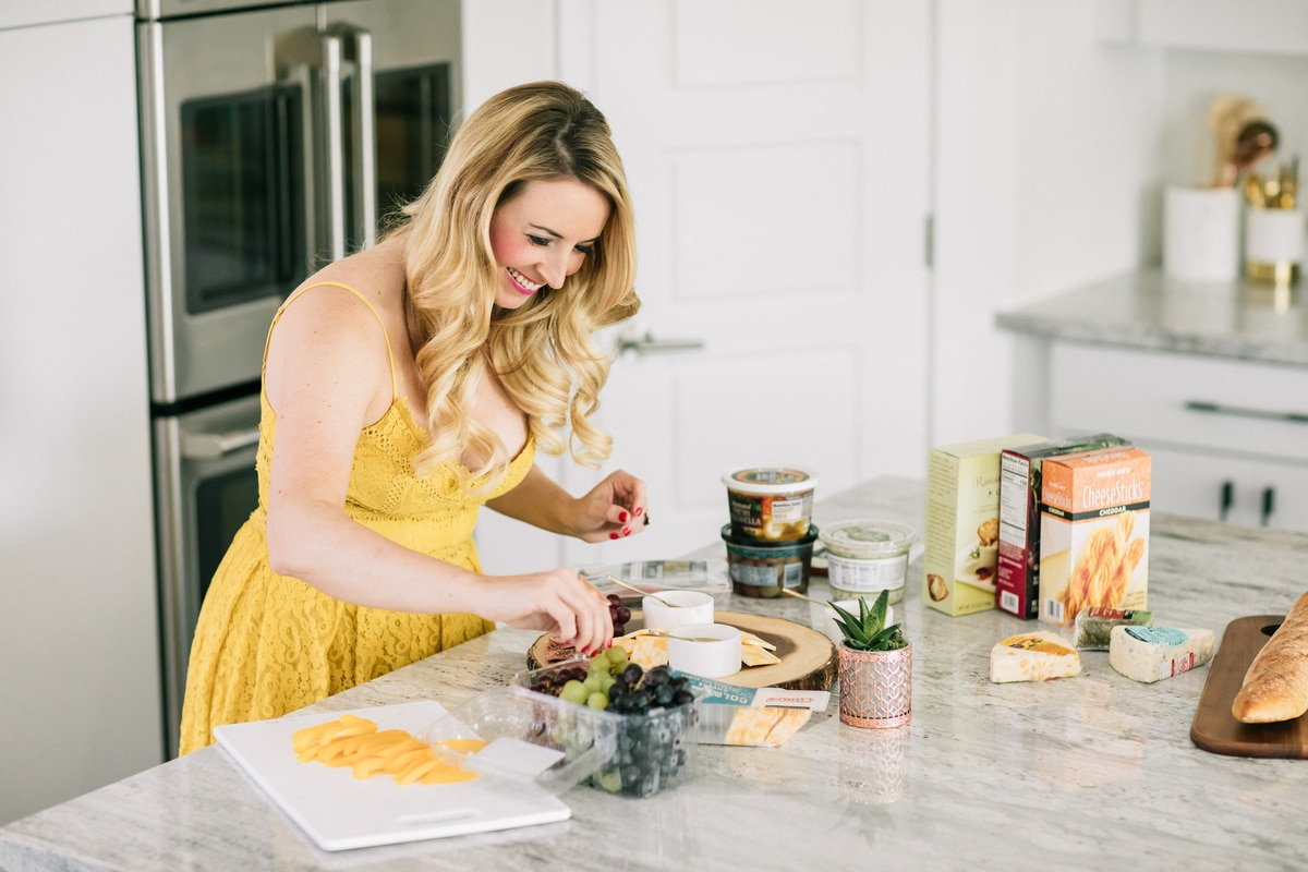 Whitney Bond making a cheese plate with grapes, olives and crackers in kitchen