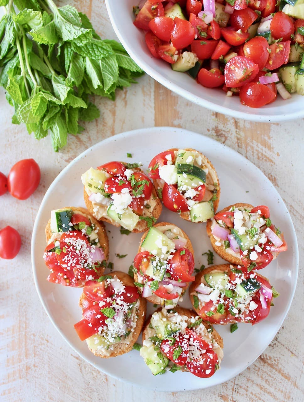 Tomato Cucumber Greek Bruschetta on Toasted Bread, topped with Garlic Hummus and Feta Cheese
