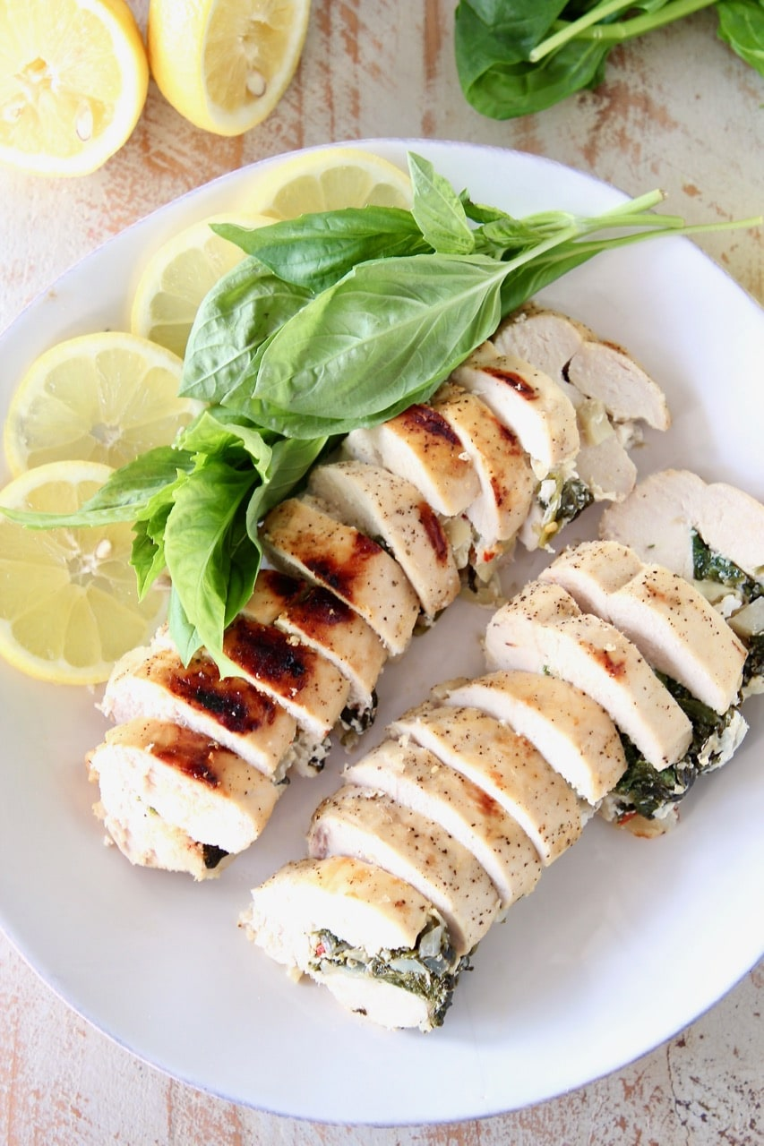 Sliced Spinach Artichoke Stuffed Chicken Breasts with Lemon Slices and Fresh Basil