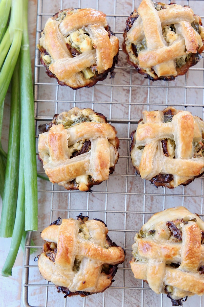 Spinach Feta Mini Pies with Braided Puff Pastry Crust on Wire Baking Rack with Green Onions