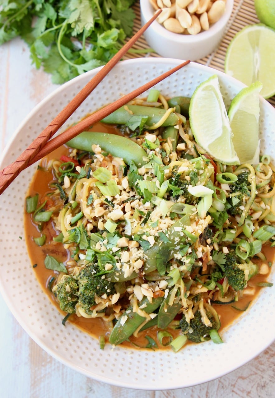 Vegan Pad Thai Recipe with Fresh Scallions, Limes, Broccoli and Cilantro in bowl with chopsticks