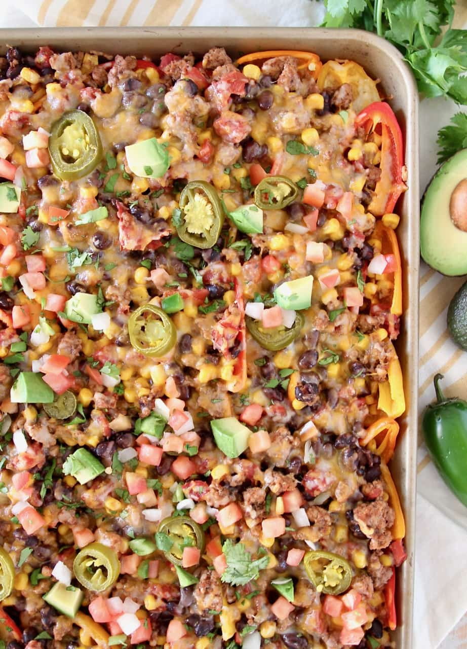 Low carb nachos on a baking sheet with avocado and jalapeno