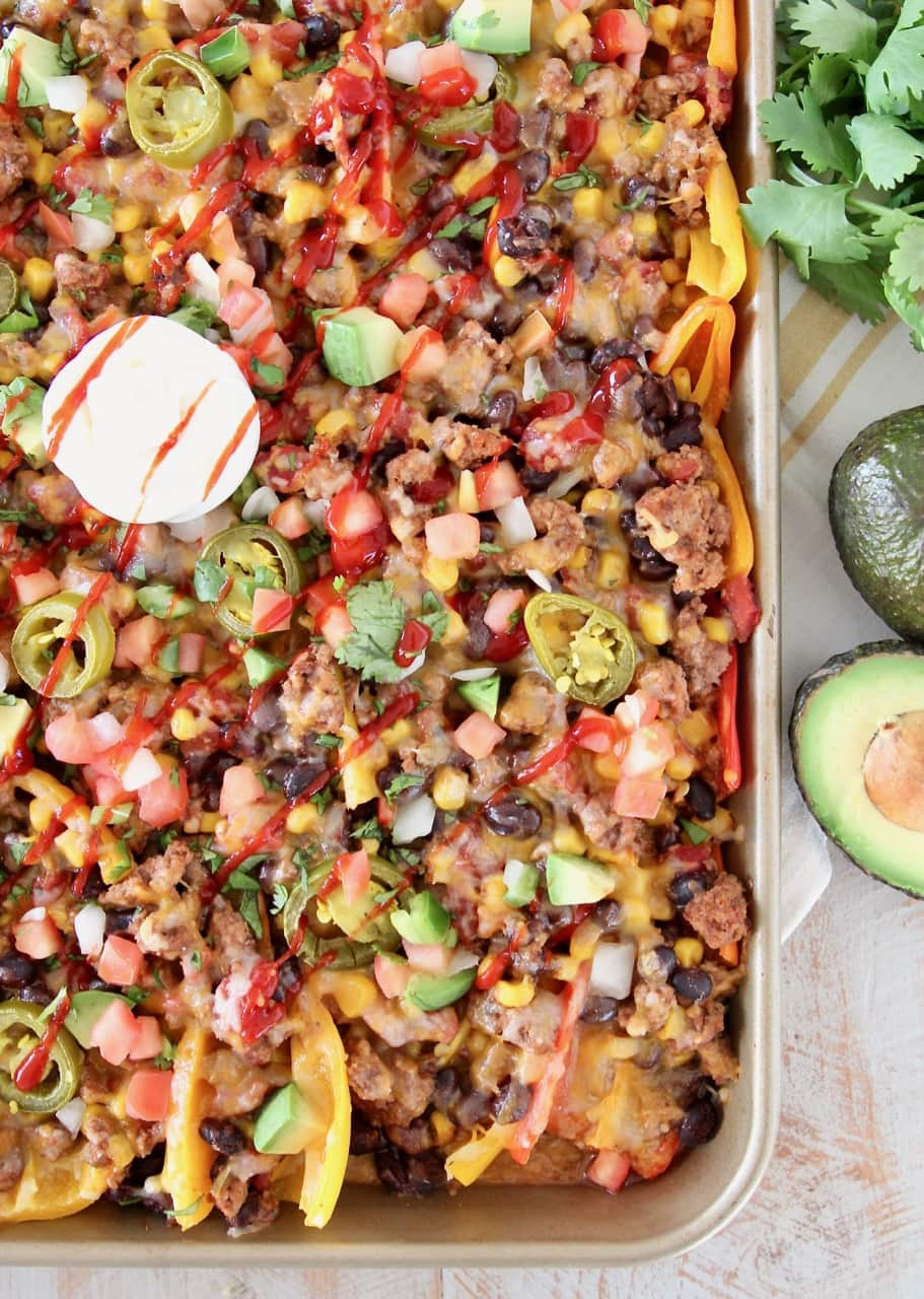 Low Carb Nachos made with sweet mini bell peppers, topped with turkey, beans, corn, tomatoes, jalapenos, avocado, hot sauce and sour cream on a baking sheet