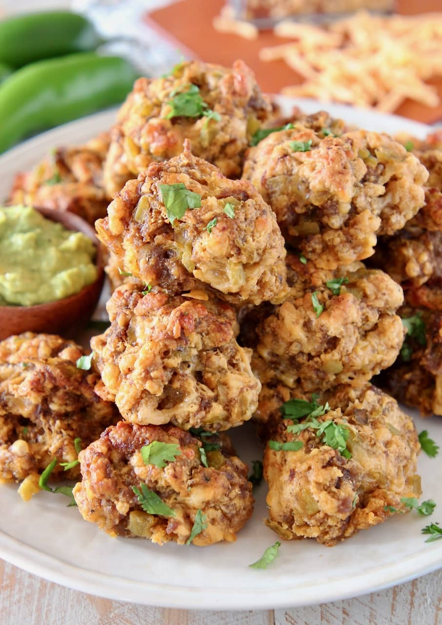 Mexican Bisquick Chorizo Sausage Balls on plate with creamy avocado sauce in small bowl