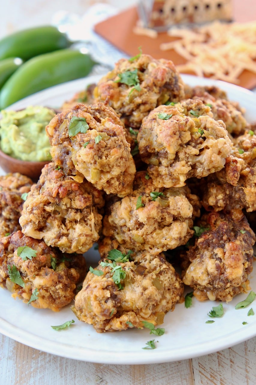 Mexican Chorizo Bisquick Sausage Balls on plate with creamy avocado sauce in small bowl, jalapenos and shredded cheddar cheese