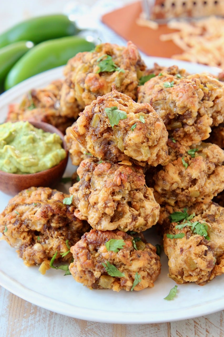 Mexican Bisquick Sausage Balls piled up on plate with small bowl of avocado dipping sauce