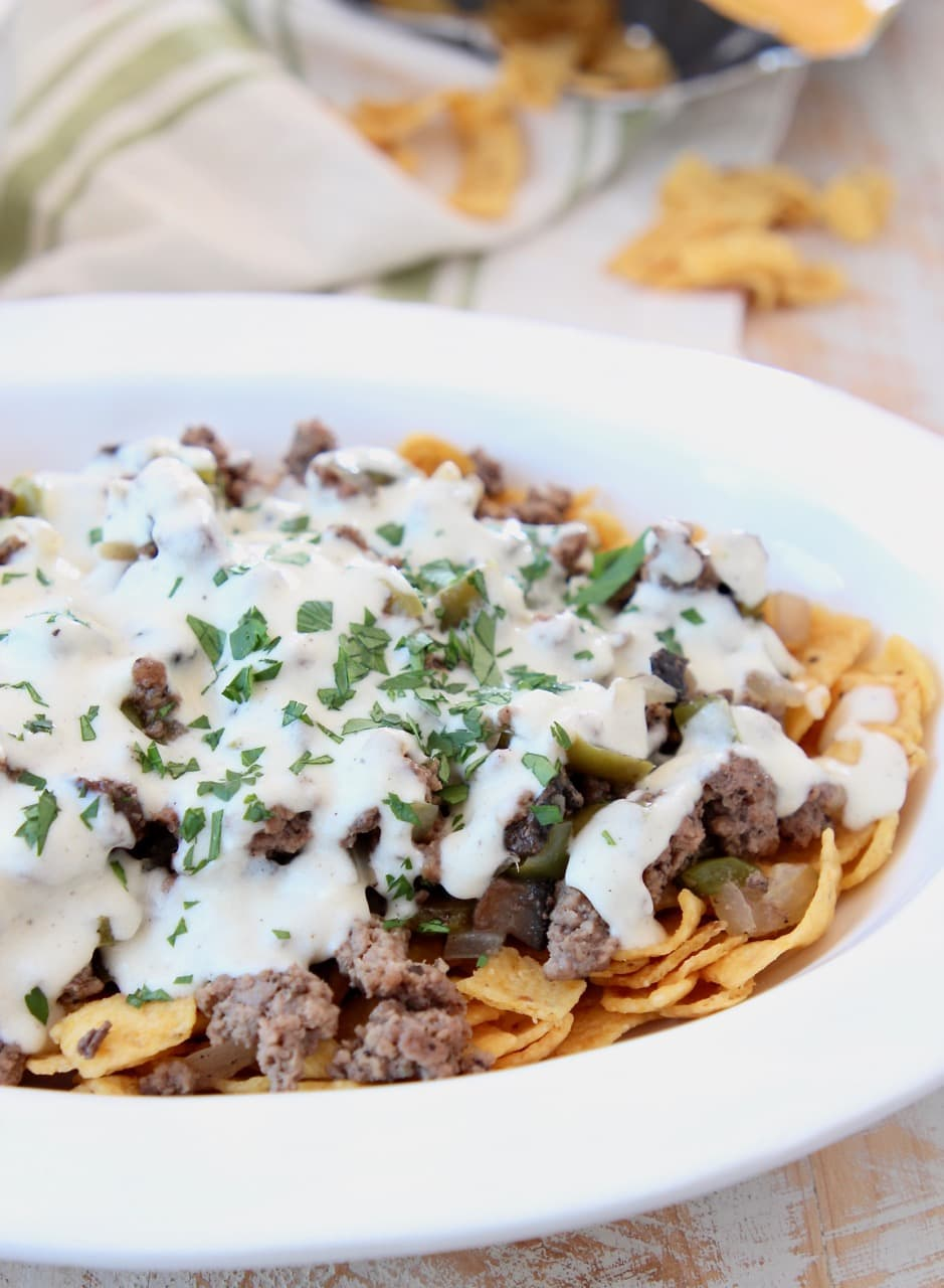 Fritos topped with ground beef and creamy provolone sauce in casserole dish
